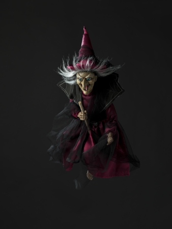 Image of a witch flying on her broomstick over dark background. Stock Photo - 17339597