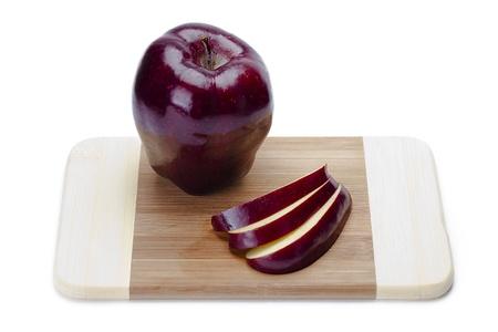 Close shot of an apple on a cutting board.