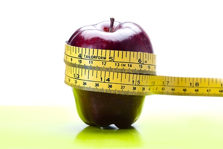 Close up of an apple on a table wit ha measuring tape around it. Stock Photo