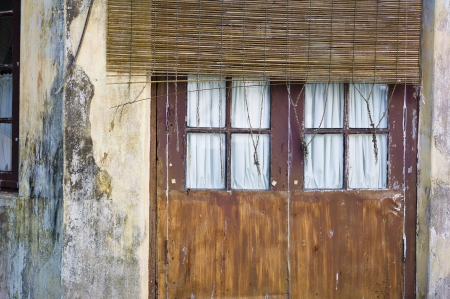 A closed door with a thatched sun blocker in front of it in Kochi, India.