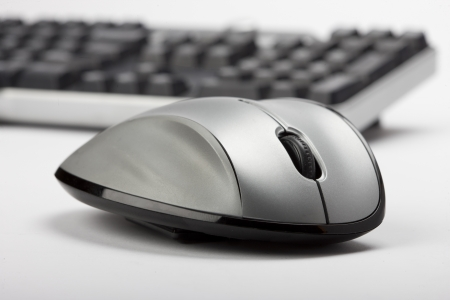 mechanical mouse: Mouse in foreground and keyboard blurred keyboard in background. Stock Photo