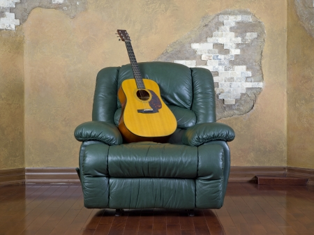 luxuries: A leather armchair with a guitar on it Stock Photo