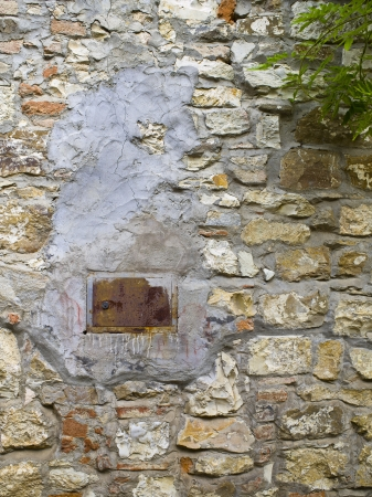 A vent set into a stone wall that is patched with cement Stock Photo - 17354567