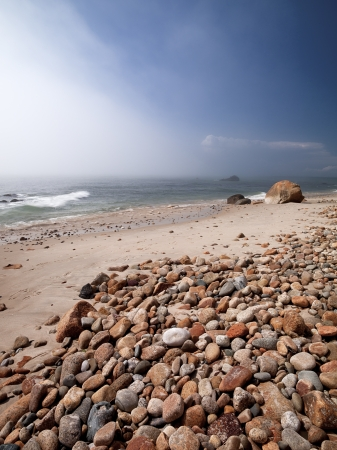 martha: Scenic view of rocks and stones at beach with sea and clear sky in background. Stock Photo