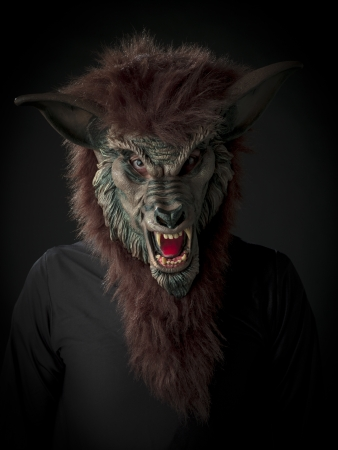 Scary werewolf against black background.