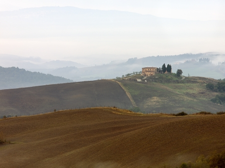 Large Tuscan villa sits atop of the hillside in the beautify Italian landscape picture. photo