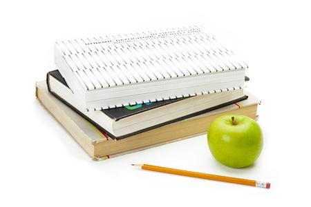 Green apple next to a set of school books. Banco de Imagens