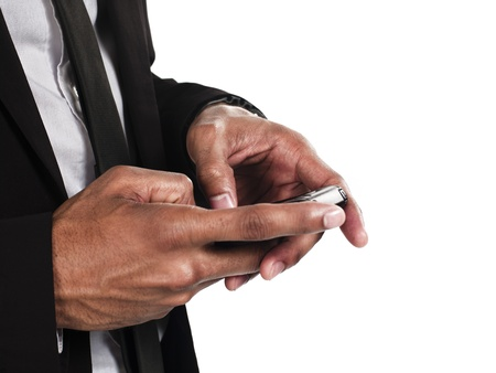 well dressed  holding: Mid section of a businessman texting against white background, Model: Kareem Duhaney Stock Photo