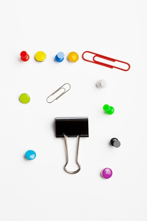 Paperclips and push pins mixed together on a white background