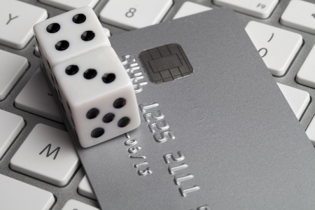 Dice on top credit card and keyboard representing gameblng over the internet. photo