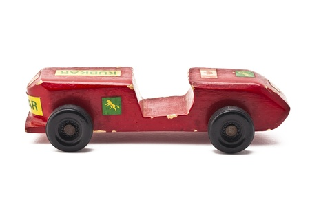Side view of a old red toy car isolated on white background. photo