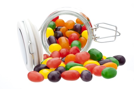jelly beans: Jelly beans spilling out of a glass jar Stock Photo