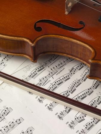 sheet music: Close up image of violin and music sheet