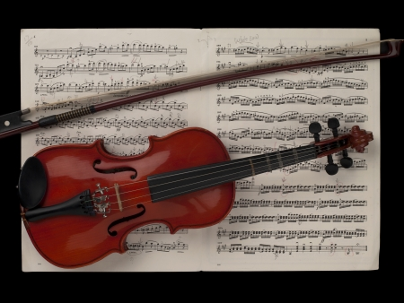 Image of violin with music sheet against black background photo
