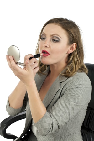 Closed up portrait of an attractive businesswoman applying lipstick while looking at her pocket mirror Stock Photo - 17353906