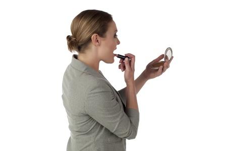 Image of businesswoman applying lipstick against white background Stock Photo - 17352124