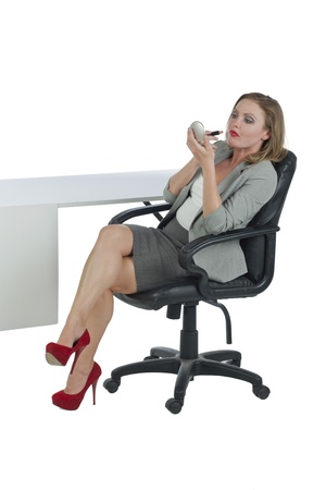 Portrait of businesswoman applying lipstick while in the office photo