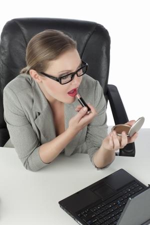 High angle shot of an attractive secretary applying lipstick Stock Photo - 17353781