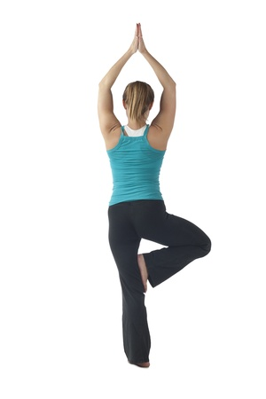 tree position: Portrait of a woman doing the tree position in yoga taken from behind