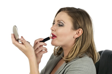 Closed up shot of a blond woman applying lipstick over a white background Stock Photo - 17352920