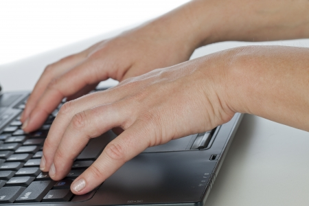 Close up of hands of a woman typing in the laptop keyboard photo