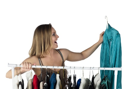 choosing clothes: Delighted woman shopper choosing clothes to buy in a clothes rack