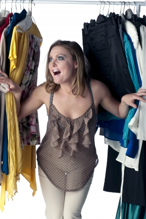 closet: Close-up shot of a delighted woman looking inside a closet full of clothes and dresses Stock Photo