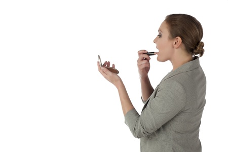 Portrait of pretty businesswoman applying make up against white background photo