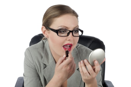 Portrait of pretty businesswoman putting lip stick against white background photo