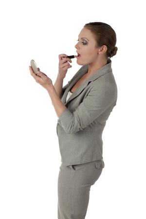 Side view image of businesswoman putting lipstick on her lips isolated over the white surface Stock Photo - 17352166
