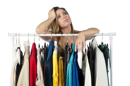 Portrait of stressed female with clothes collection against white background