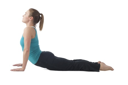 Portrait of young woman practicing yoga exercise against white background photo