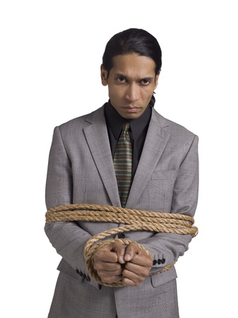 Portrait of businessman wrapped up with brown rope against white background photo