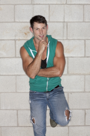sleeveless hoodie: Portrait of an attractive male standing with one leg while leaning on the wall