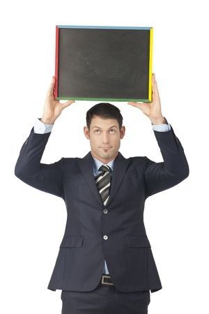 Portrait of businessman raising an empty blackboard over a white background photo