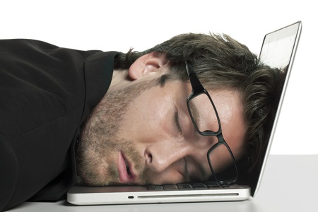 tired businessman: Close-up image of tired businessman sleeping on his laptop against the white surface