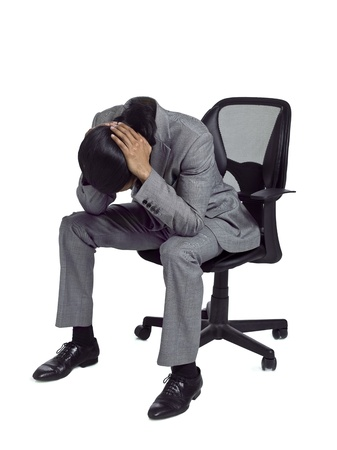 Disappointed businessman sitting on an office chair with his head down Stock Photo - 17367378