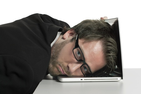 burn out: Portrait of exhausted businessman leaning on his laptop Stock Photo