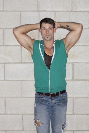 hooded vest: Portrait of good looking guy gesturing a pose leaning wall