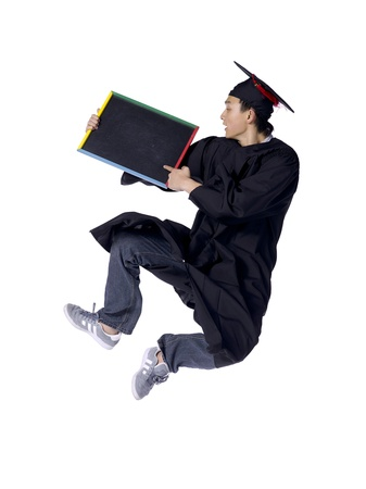 Portrait of graduating student jumping while holding black board against white background Stock Photo - 17368443