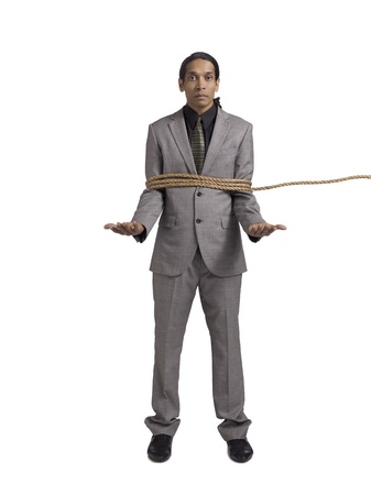 Portrait of helpless businessman tied up against white background photo