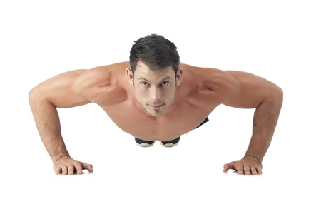 Portrait of macho man doing push up while lying on a white surface photo