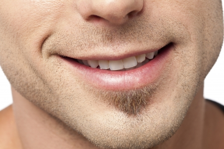 Close up image of male lips with a smile against white background
