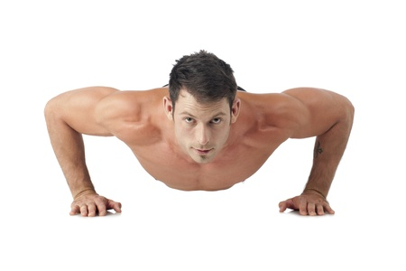 Close-up image of muscular man doing push up on a white surface photo
