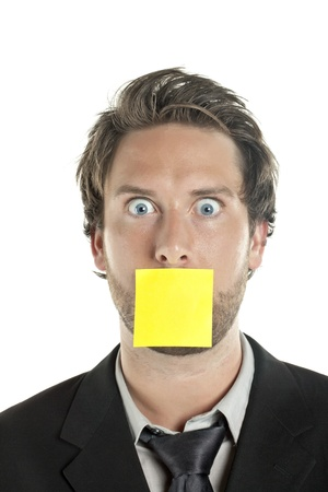 Portrait of shocked businessman with a sticky note covering his mouth photo
