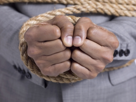 Closeup shot of a businessman's hands tied with rope Stock Photo - 17400429
