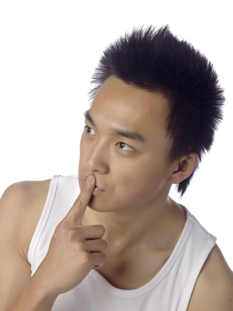 Close-up image of a young man in a silence gesture looking at the side of a white background photo