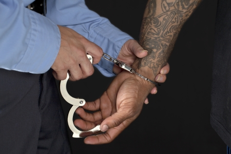 Closeup shot of a police officer handcuffing a man