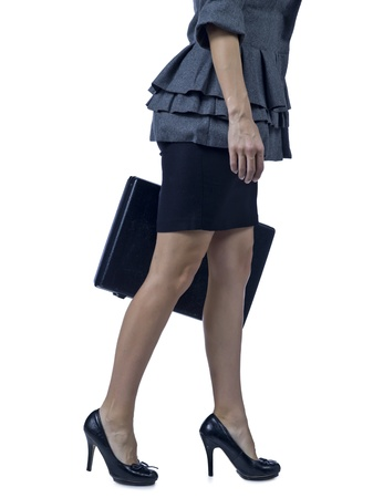 Unrecognized businesswoman with briefcase walking on a white background photo