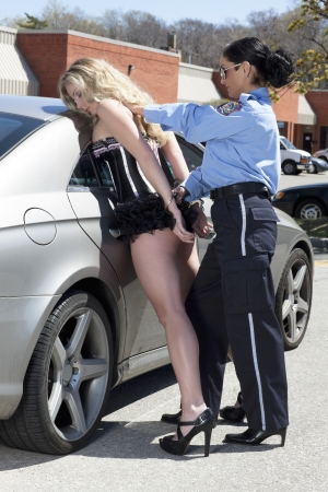Police woman handcuffing the woman photo